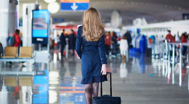 Air hostess wheeling suitcase through airport